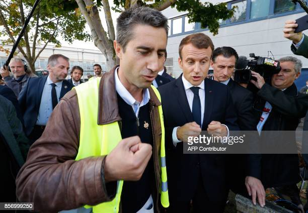 TOPSHOT La France Insoumise leftist party's MP Francois Ruffin and French President Emmanuel Macron gesture as they talk during a visit to the...