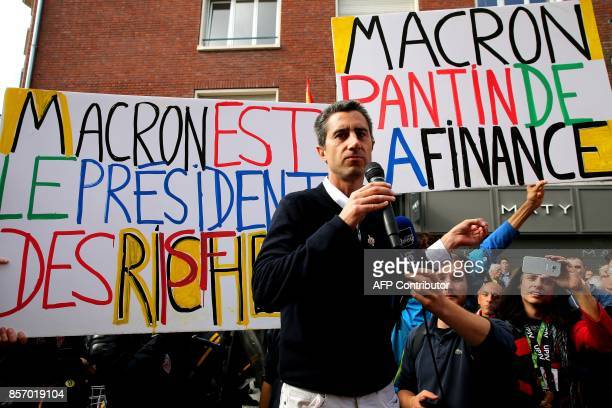 La France Insoumise leftist party's MP Francois Ruffin looks on next to a sign reading 'Macron puppet of the finance' and 'Macron president of rich...