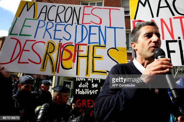La France Insoumise leftist party's MP Francois Ruffin speaks next to policemen and a sign reading 'Macron president of the riche people' during a...