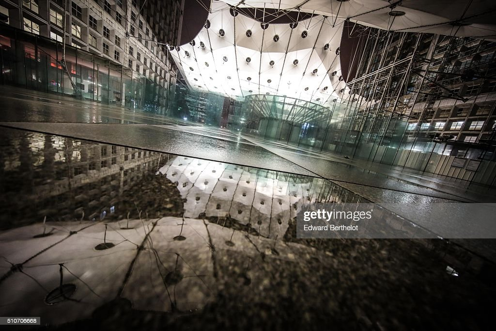 La Grande Arche de la Defense reflecting into a puddle on February 13, 2016 in Paris La Defense, France.