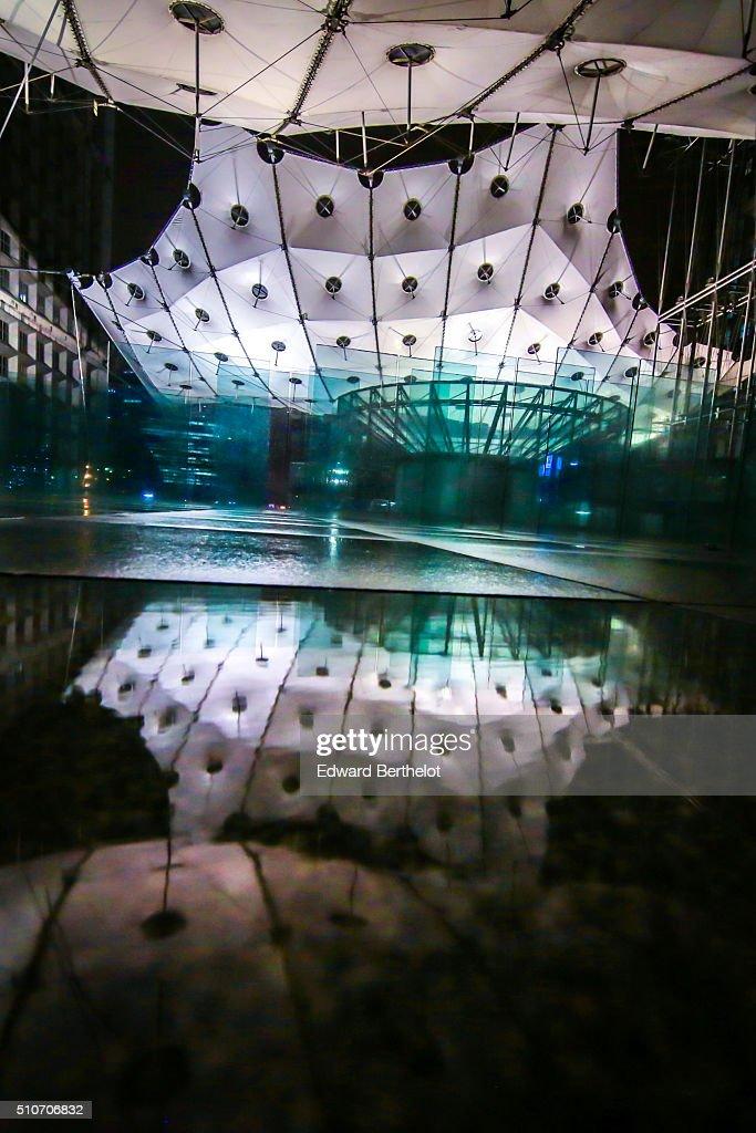 La Grande Arche de la Defense reflecting into a puddle on February 13, 2016 in Paris La Defense, France.