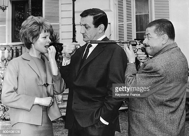 La jeune actrice Sabine Singen et Lino Ventura impassibles tandis que Francis Blanche vise de son pistolet la jeune fille dans 'Les Tontons...