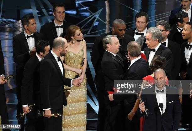 La La Land' producer Fred Berger speaks at the microphone as production staff consult behind him regarding a presentation error of the Best Picture...