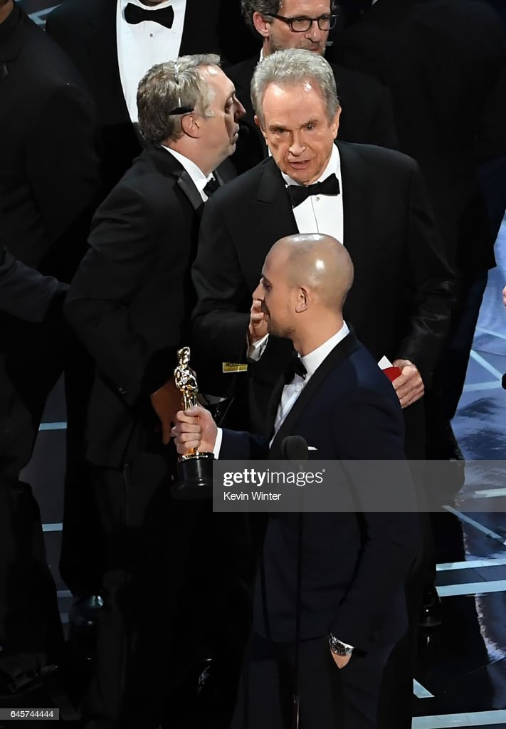 'La La Land' producer Fred Berger (C) speaks at the microphone as production staffer and actor Warren Beatty consult behind him regarding a presentation error of the Best Picture award (later awarded to 'Moonlight') onstage during the 89th Annual Academy Awards at Hollywood & Highland Center on February 26, 2017 in Hollywood, California.
