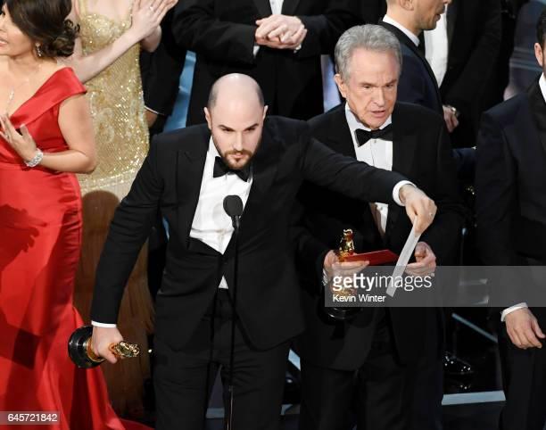 'La La Land' producer Jordan Horowitz holds up the winner card reading actual Best Picture winner 'Moonlight' with actor Warren Beatty onstage during...