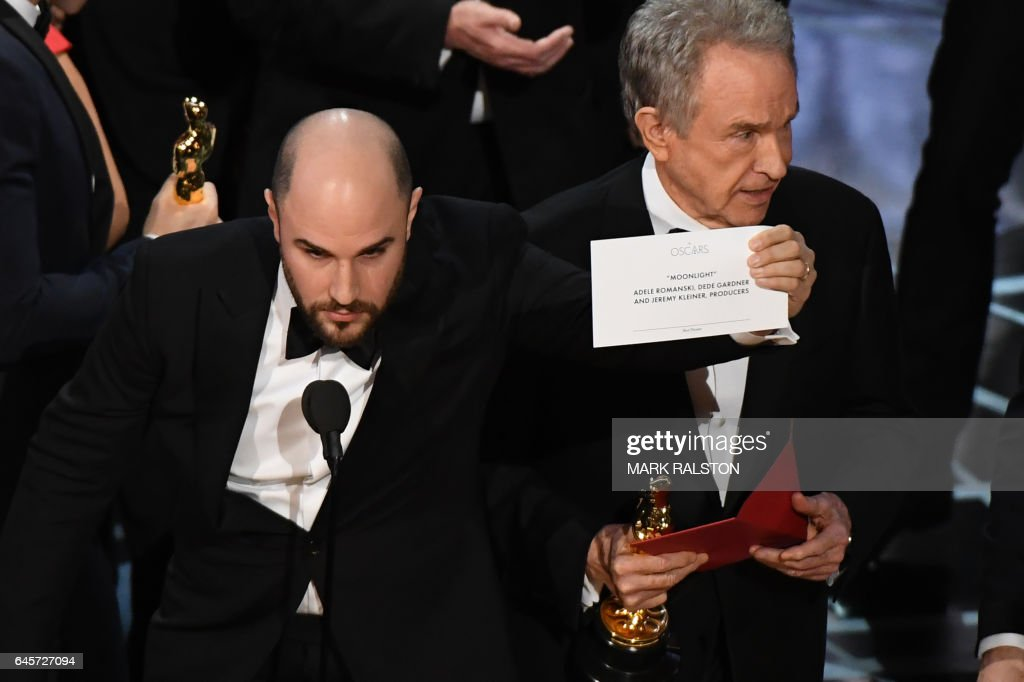 TOPSHOT - 'La La Land' producer Jordan Horowitz (L) shows the card reading Best Film 'Moonlight' next to US actor Warren Beatty after the latter mistakingly read 'La La Land' initially at the 89th Oscars on February 26, 2017 in Hollywood, California. / AFP PHOTO / Mark RALSTON