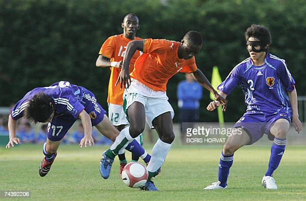 Japan defenders Atomu Tanaka and Atsuto Uchida vies with Ivory Coast's forwards Kader Toure and Adama Traore during their under 21 international...