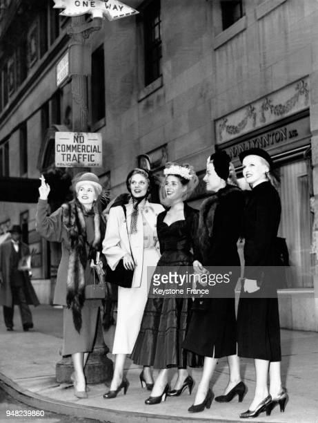 La mannequin française Lise Bourdin au centre en robe de taffetas noir et voilette visite la ville en compagnie de jeunes modèles américains à New...