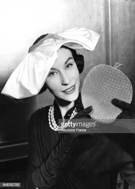 La mannequin Myrtle Crawford présente le modèle 'Rendezvous' en velours rose et doré avec une 'couronne' amovible présentée dans ses mains lors d'une...
