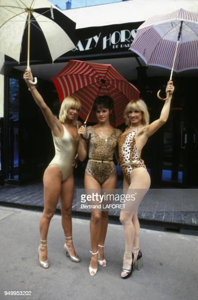 La meneuse de revue Lova Moor, à gauche, et deux autres danseuses posent en body devant le cabaret Crazy Horse, circa 1980, à Paris, France.