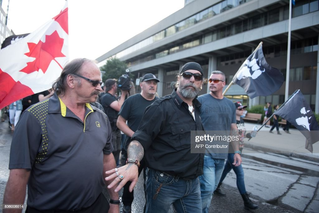 La Meute, a far-right, anti-immigration group, holds a rally in Quebec City, Canada, on August 20, 2017. Clashes erupted Sunday between police and dozens of anti-racist activists on the sidelines of a pro-immigration rally in Quebec City while a demonstration organized by extreme-right activists gained little traction. In a bid to keep the two rallies apart, police erected a security cordon but declared the anti-racist demonstration illegal after sporadic clashes broke out and hooded individuals threw projectiles at police. PHOTO / Alice Chiche