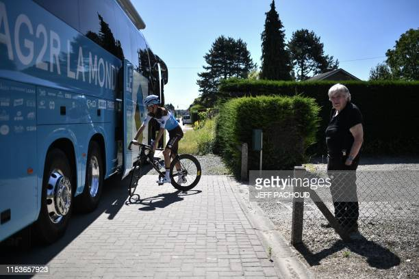 La Mondiale's French rider Romain Bardet rides past the team's bus before a training session near Brussels on July 4 two days prior to the start of...