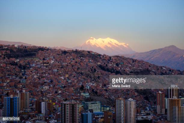 la paz - cityscape with illimani volcano in background at sunset - capital cities stock photos and pictures