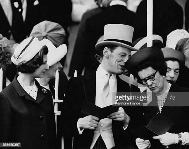 La Princesse Alexandra,regarde son epoux Angus Ogilvy parler a l'oreille de sa mere la Duchesse Marina de Kent lors du Derby le 2 juin 1965 a Epsom,...