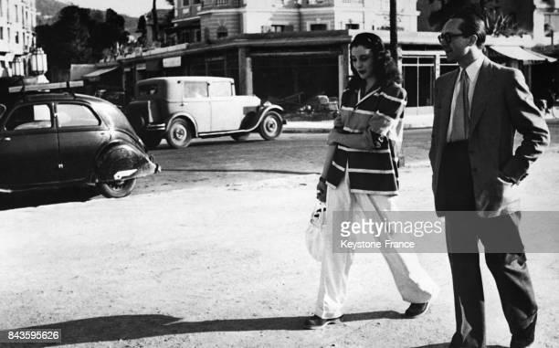 La princesse Faouzia Faoud soeur du roi Farouk d'Egypte accompagnée du comte Charles Emmanuel de la Rochefoucauld se promène sur la croisette à...