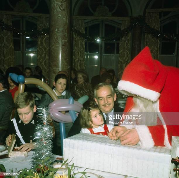 La princesse Stéphanie en compagnie de son père le prince Rainier découvre le cadeau que lui offre le Père Noël à gauche le prince Albert ouvre son...