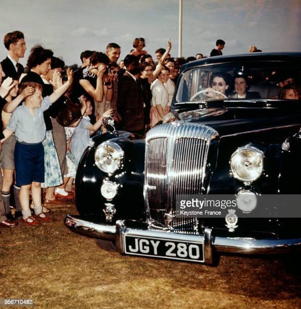 La reine Elizabeth au volant de sa voiture est saluée par la foule au RoyaumeUni