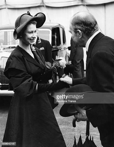 La Reine tenant dans la main une rose salue Lord Aberconway, President de la Royal Horticultural Society, apres sa visite au Salon de la Fleur le 22...