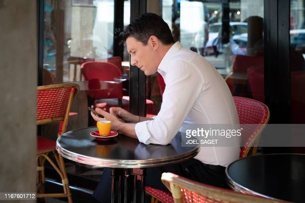 La Republique en Marche candidate for the Paris 2020 mayoral election Benjamin Griveaux looks at a smartphone while sitting in a cafe in Paris on...