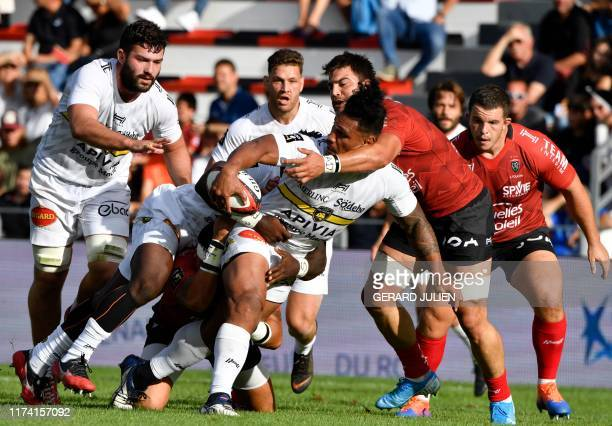 La Rochelle's Australian flanker Lopeti Timani passes the ball as he gets tackled during the French Top 14 rugby union match between Toulon and La...