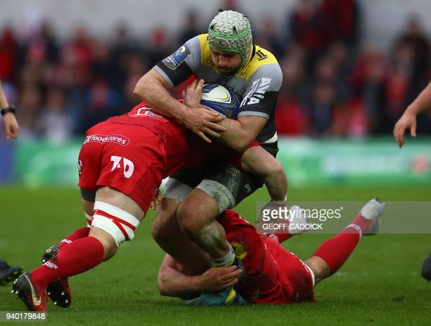 La Rochelle's French Kevin Gourdon is tackled by Scarlets' Welsh Will Boyde and Scarlets' Welsh Lewis Rawlins during the European Champions Cup rugby...