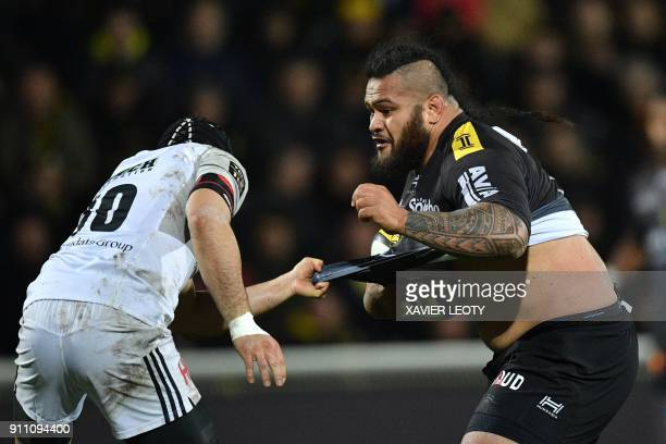 La Rochelle's French prop Vincent Pelo has his jersey pulled as he runs with the ball during the French Top 14 rugby union match between La Rochelle...
