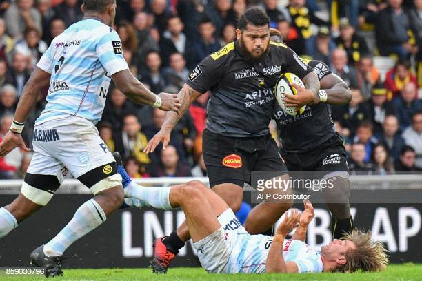 La Rochelle's French prop Vincent Pelo runs with the ball as Racing 92 hooker Dimitri Szarzewski falls during the French Top 14 rugby union match...
