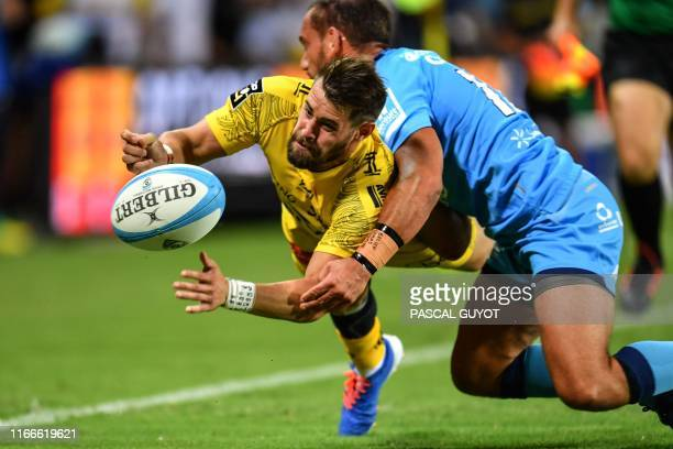 La Rochelle's French wing Arthur Retiere is tackled by Montpellier's New Zealander flyhalf Aaron Cruden during the French Top 14 rugby union match...