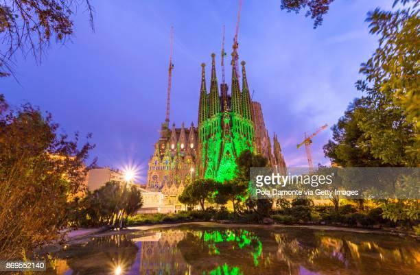 La Sagrada Familia church designed by Antoni Gaudi illuminated at night. UNESCO World Heritage Site, reflected in pond, Barcelona, Catalonia, Spain.