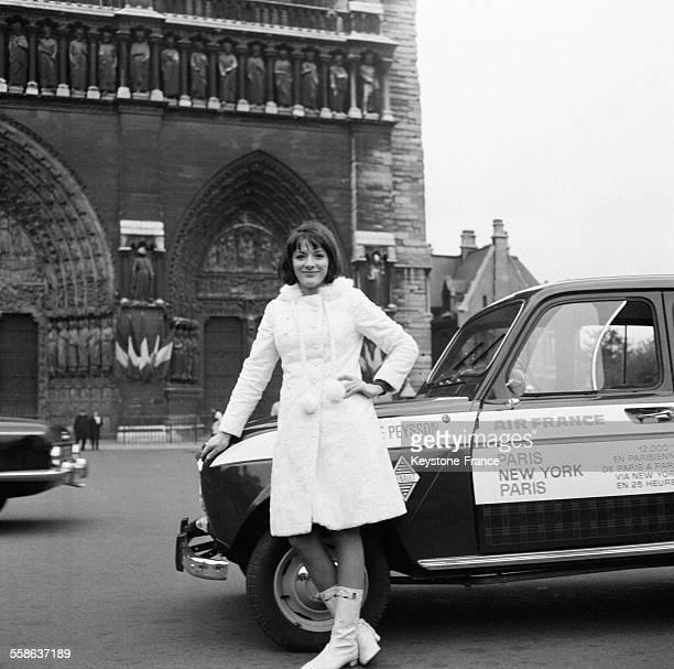 La speakerine AnneMarie Peysson avec sa voiture devant la Cathédrale NotreDame après avoir gagné le pari que lui avait lancé le présentateur Guy Lux...