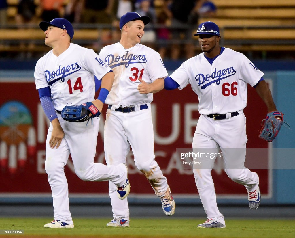 la66#2, Joc Pederson #31 and Enrique Hernandez #14 of the Los Angeles Dodgers celebrate the final out of the game and a 6-3 win over the New York Mets at Dodger Stadium on June 22, 2017 in Los Angeles, California.