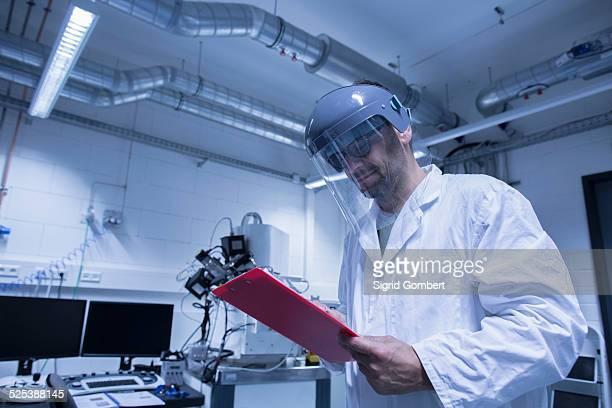 lab assistant checking details on clipboard - sigrid gombert stockfoto's en -beelden