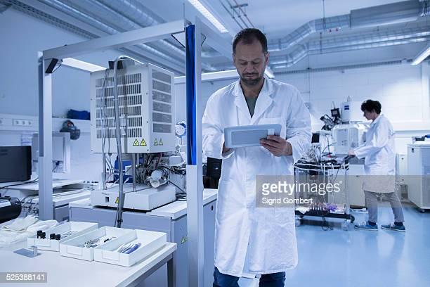 lab assistant checking details on digital tablet - sigrid gombert stock-fotos und bilder