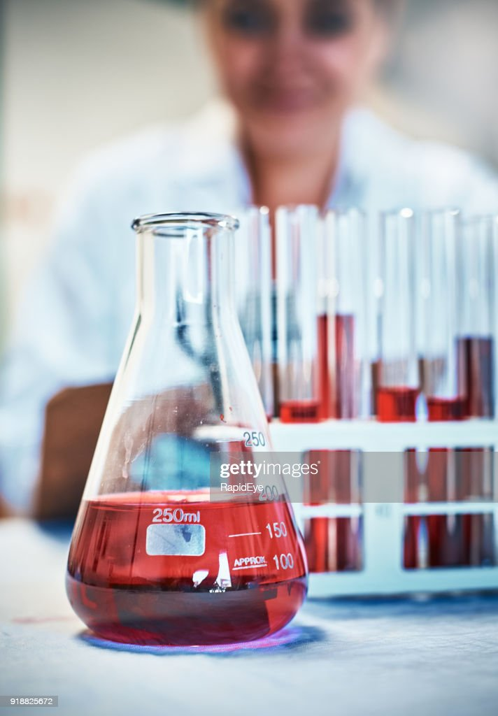 Lab flask and test tubes with red liquid, scientist behind : Stock Photo