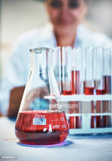 lab flask and test tubes with red liquid, scientist behind - volume fluid capacity stock pictures, royalty-free photos & images