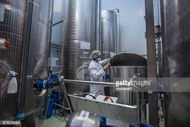 Lab technician in pharmaceutical plant in front of tanks