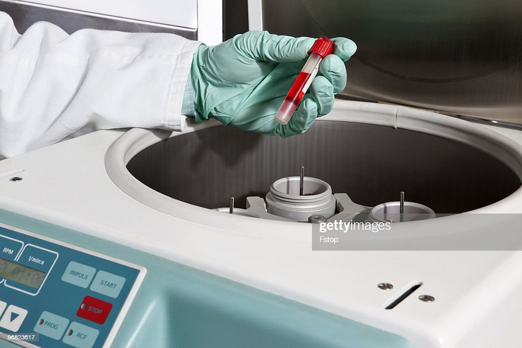 A lab technician putting a test tube into a centri : Stock Photo