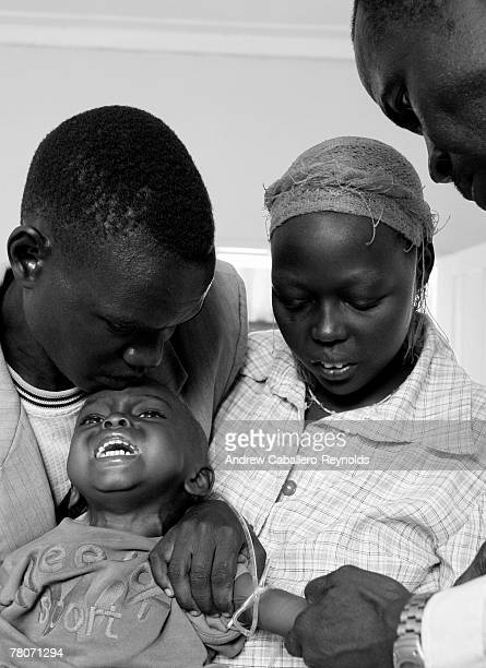 A lab technician takes blood from a young boy as his parents hold him down to test for traces of the Kala Azar parasite at a clinic November 16 2006...