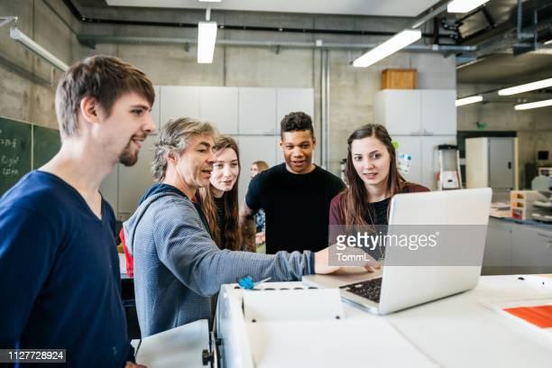 laborantin im gespräch mit studenten vor laptop - anleitung konzepte stock-fotos und bilder
