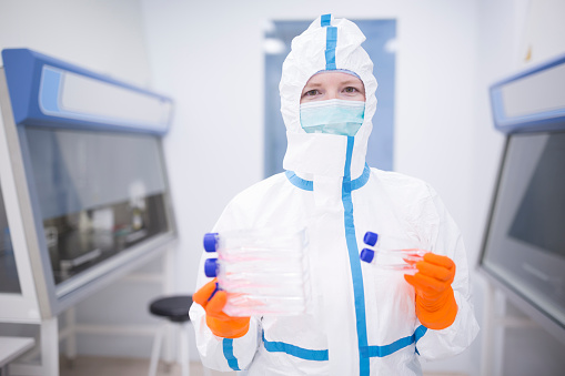 Lab technician wearing cleanroom overall holding cultivation containers - gettyimageskorea
