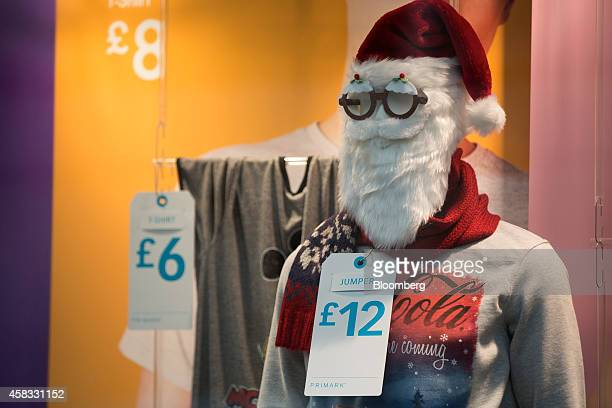 A label displays the price in pounds as a mannequin displays Santa themed seasonal accessories in the window display of a Primark clothing store...