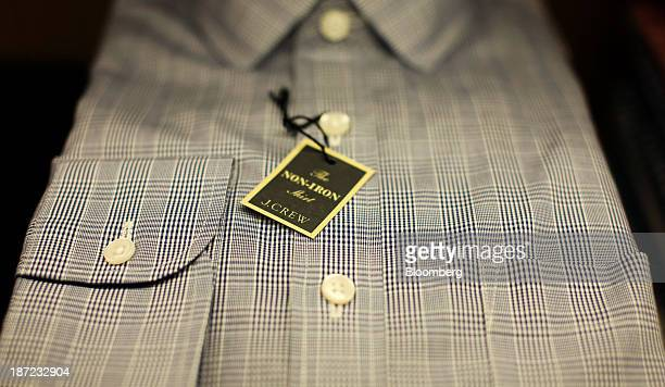A label hangs from a men's checked shirt inside a J Crew Group Inc store in London UK on Thursday Nov 7 2013 J Crew Group Inc is enriching owners led...