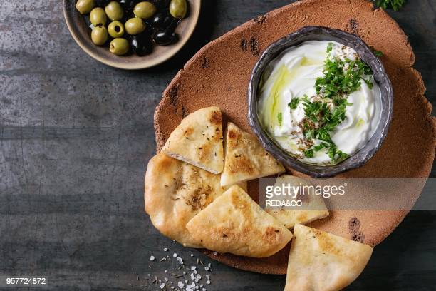 labneh middle eastern lebanese cream cheese dip with olive oil salt herbs served with olives traditional pita bread on terracotta plate over dark...