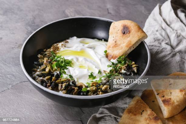 labneh middle eastern lebanese cream cheese dip with olive oil salt herbs olives tapenade served in black bowl with traditional pita bread over gray...