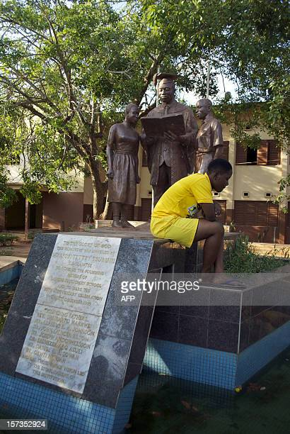 Labone Senior High School student sits next to a statue on the school grounds on December 1 2012 in Accra Ghana's main opposition presidential...