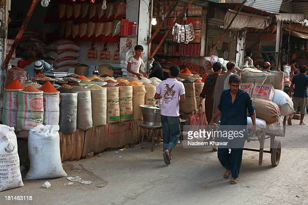 Labor pulling hand cart to deliver the luggage in Streets of Lahore. Daily routine work in the narrow streets of Down town and spice market of Akbari...
