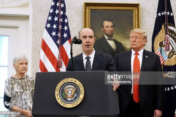 Labor Secretary Eugene Scalia delivers remarks while standing in between his mother Maureen Scalia and US President Donald Trump before Scalia is...