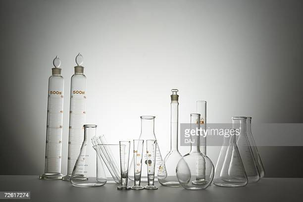Laboratory bottles and graduated cylinders, front view, gray background