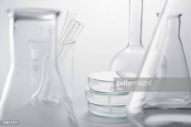 Laboratory bottles and test tubes, white background, differential focus