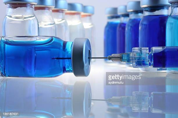 laboratory bottles with blue content and a syringe - vial stock pictures, royalty-free photos & images